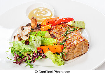 Grilled pork meat and vegetables on plate