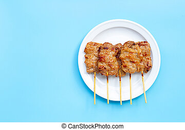 Grilled pork on white plate on blue background. Copy space
