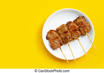 Grilled pork on white plate on yellow background.
