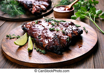 Grilled pork ribs on wooden board, shallow depth of field