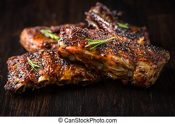 Grilled pork spare ribs with rosemary on wooden background.
