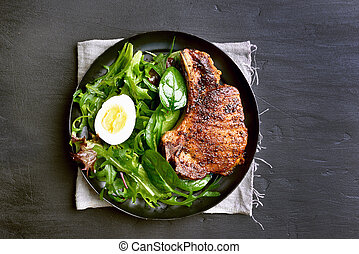 Grilled pork steak with green salad in plate on dark background with copy space, top view