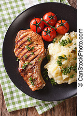 Grilled pork steak with mashed potatoes close-up. Vertical top view