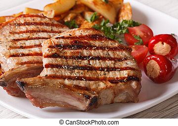 Grilled pork steak with potatoes and vegetables on a plate, ...