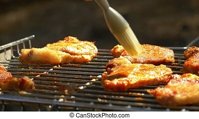 Grilled pork steaks over flames and coals, on the brazier,...