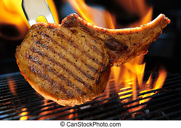 Grilled pork chop on the flaming grill