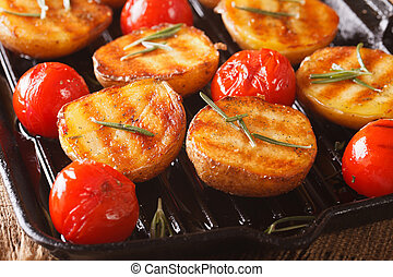 Grilled potatoes and tomatoes with rosemary macro on the grill pan. Horizontal