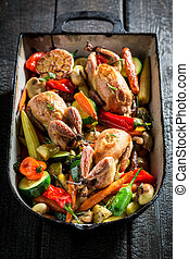 Grilled quails with vegetables in casserole on dark background