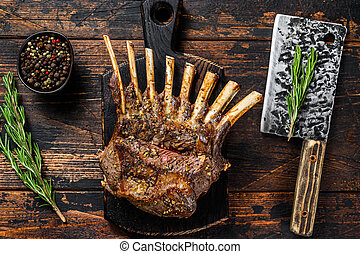Grilled rack ribs of lamb meat chops. Dark wooden background. Top view
