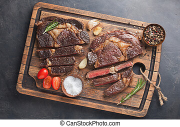Grilled ribeye beef steak, herbs and spices on a dark stone background. Top view with copy space for your text