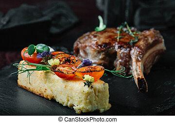 Grilled ribeye steak with polenta on dark background