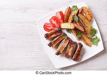 Grilled ribs, potatoes and tomatoes horizontal top view