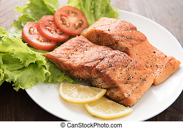 Grilled salmon fillet cooked BBQ and served with fresh herbs and