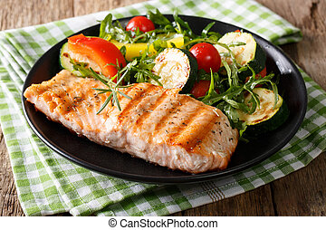 grilled salmon fillet with salad of zucchini, arugula, pepper and tomatoes close-up. horizontal