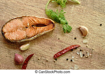grilled salmon fish with salt and pepper on wooden background