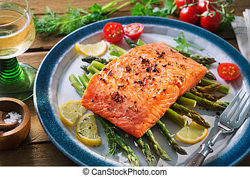 Grilled salmon garnished with green asparagus and tomatoes. ...