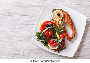 Grilled salmon steak and salad on a plate. horizontal top view