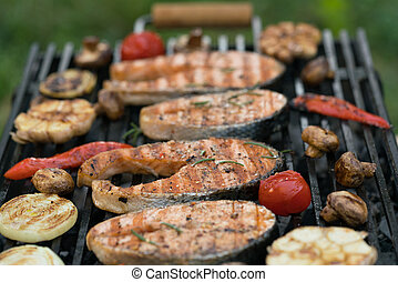 grilled salmon steaks with vegetables on the grill
