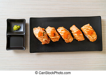 grilled salmon sushi on black plate