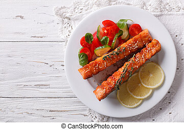 Grilled salmon with lemon and fresh salad on a plate....