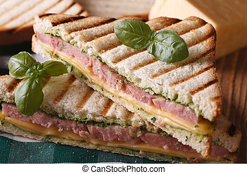 Grilled sandwich with ham, cheese and basil closeup