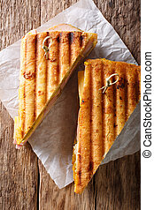 Grilled sandwich with ham, mustard, cheese, close-up on paper on the table. vertical view from above