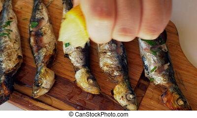 Grilled sardines with lemon juice - Close-up shot of grilled...