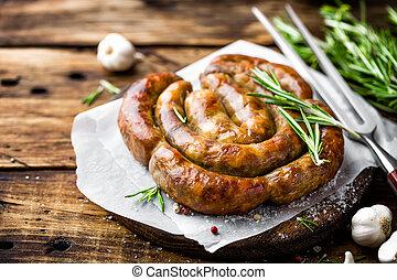 Grilled sausage on dark rustic wooden background