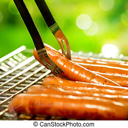 Grilled Sausage on the flaming Grill. BBQ. Barbecue outdoors