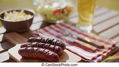 Grilled sausages and salads for a summer picnic - Grilled...