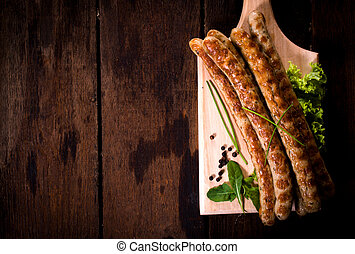 Grilled sausages on wooden board from above with blank space...