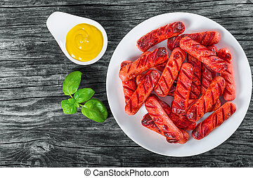 Grilled sausages on a white dish, top view