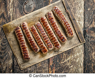 Grilled sausages on wooden table.