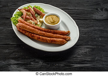 Grilled sausages over dark wooden background.