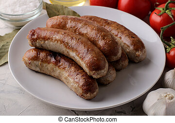Grilled sausages with tomatoes, sunflower oil and garlic on a light background
