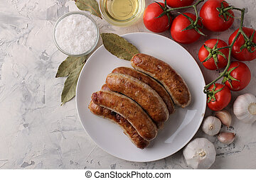 Grilled sausages with tomatoes, sunflower oil and garlic on a light background. top view