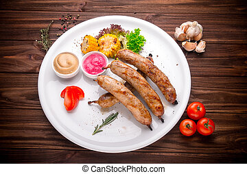 Grilled sausages with vegetables and seasoning on wood