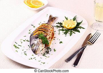 Grilled sea bream fish, lemon, arugula on plate - Grilled...