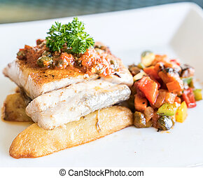 Grilled seabass fish with grilled vegetable on fries