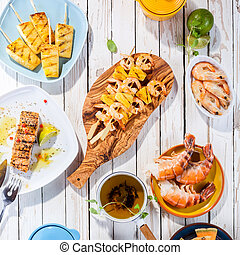 Grilled Seafood Dishes on White Wooden Table