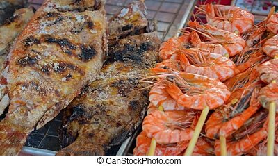 Grilled seafood, including shrimp kabobs and skewered, salt encrusted, whole tilapia, for sale at an outdoor public market in Thailand. 4k UltraHD footage