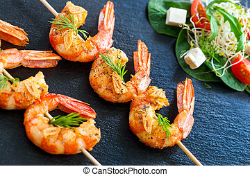 Extreme close up of grilled queen prawn brochettes spiced with natural herbs.