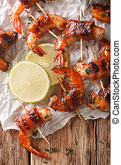 Grilled shrimp with bacon, thyme and lime close up on the table. Vertical top view
