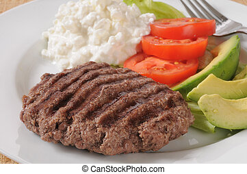 Closeup of a grilled sirloin patty with avocado and cottage cheese