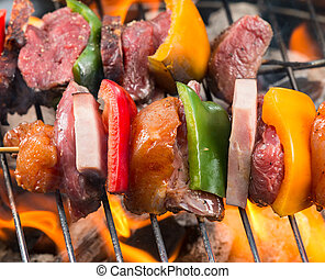 Grilled skewer on fire - Meat and vegetable skewer on...