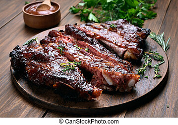 Grilled sliced barbecue pork ribs on wooden board