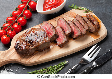 Grilled sliced beef steak on cutting board over stone table