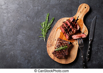 Grilled sliced beef steak on cutting board over stone table...