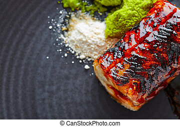 Grilled smoked eel on black plate - Grilled smoked eel with...