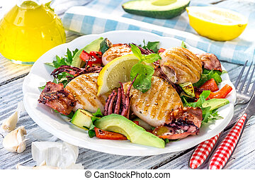 Grilled squids with vegetable on wooden background
